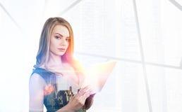 Blonde Frau mit einer Tablette und einem Stadtbild Stockbilder