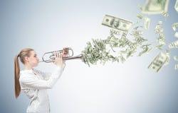 Blonde Frau mit einer Trompete und Dollarscheinen Stockfotos