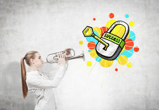 Blonde Frau mit einer Trompete und einem Erfolgsschlüssel Lizenzfreie Stockfotografie