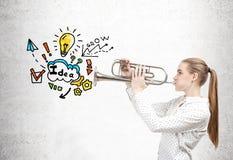 Blonde Frau mit einer Trompete und einer Geschäftsidee Lizenzfreie Stockbilder