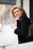 Blonde Frau mit Einkaufstaschen Stockfoto