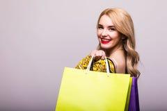 Blonde Frau mit Einkaufstaschen auf grauem Hintergrund Stockbild