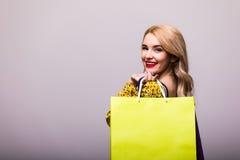 Blonde Frau mit Einkaufstaschen auf grauem Hintergrund Lizenzfreie Stockfotos