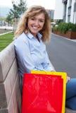 Blonde Frau mit Einkaufstaschen in der Stadt Lizenzfreie Stockbilder