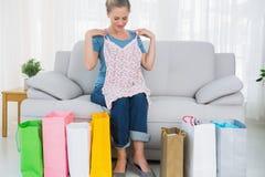 Blonde Frau mit Einkaufstaschen eine Spitze ausprobierend Lizenzfreie Stockfotografie