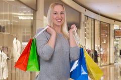 Blonde Frau mit Einkaufstaschen in einem Einkaufszentrum Lizenzfreies Stockbild