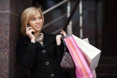 Blonde Frau mit Einkaufstaschen um das Telefon ersuchend Stockfotografie