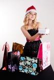 Blonde Frau mit Einkaufstaschen und Geschenk Stockfoto