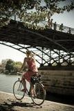 Blonde Frau mit Fahrrad unter der Brücke von Künsten in Paris Lizenzfreies Stockfoto