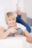 Blonde Frau mit Fernbedienung Stockfoto