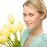 Blonde Frau mit gelben Tulpenfrühlingsblumen Lizenzfreie Stockbilder