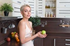 Blonde Frau mit grünem Apfel Lizenzfreie Stockfotografie
