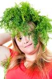 Blonde Frau mit grünen Karottentrieb auf Kopf Stockfotografie
