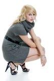 Blonde Frau mit grauem Kleid hockend Lizenzfreie Stockfotografie