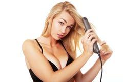 Blonde Frau mit Haarstrecker Stockfoto
