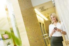 Blonde Frau mit Handy im Büro Lizenzfreie Stockbilder