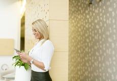 Blonde Frau mit Handy im Büro Stockfotos