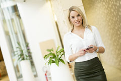 Blonde Frau mit Handy im Büro Lizenzfreie Stockfotografie