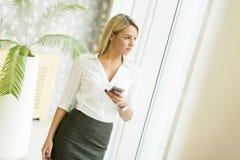 Blonde Frau mit Handy im Büro Lizenzfreies Stockbild