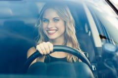 Blonde Frau mit hellem Lächeln hinter dem Rad des Autos Stockfotografie
