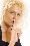 Blonde Frau mit ihrem Finger bis zu ihren Lippen Stockfoto