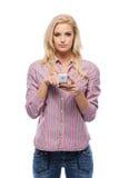 Blonde Frau mit ihrem Mobiltelefon im Studio Stockfoto
