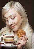 Blonde Frau mit Kaffee und Plätzchen Lizenzfreie Stockfotos