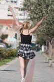 Blonde Frau mit kleinen Zöpfen laufen in Bürgersteigsstadtbild am Hintergrund Lizenzfreies Stockbild