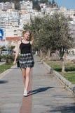 Blonde Frau mit kleinen Zöpfen laufen in Bürgersteigsstadtbild am Hintergrund Stockbilder