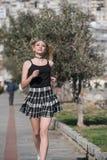 Blonde Frau mit kleinen Zöpfen laufen in Bürgersteigsstadtbild am Hintergrund Stockfotos