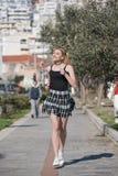 Blonde Frau mit kleinen Zöpfen laufen in Bürgersteigsstadtbild am Hintergrund Stockfoto