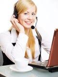 Blonde Frau mit Kopfhörer im Büro Stockfoto