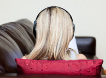 Blonde Frau mit Kopfhörern auf dem Lügen auf einem Sofa Lizenzfreie Stockfotografie