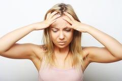 Blonde Frau mit Kopfschmerzen, die Kopf halten Stockfoto