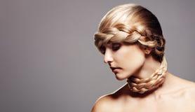 Blonde Frau mit kreativer Zopffrisur Stockfoto
