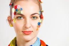 Blonde Frau mit Kreativitätsfrisur mit farbigen Knöpfen und f Stockbilder