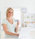Blonde Frau mit Kreditkarte und Notizbuch Stockfotos
