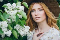 Blonde Frau mit lila Blumen im Frühjahr Stockbilder