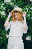Blonde Frau mit lila Blumen im Frühjahr Lizenzfreie Stockfotos