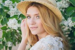 Blonde Frau mit lila Blumen im Frühjahr Lizenzfreie Stockbilder