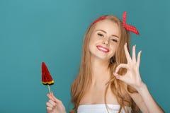 Blonde Frau mit Lutscherblauhintergrund Lizenzfreie Stockbilder