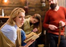Blonde Frau mit misstrauischem Blicklesebuch Frau im blauen Hemd und in den Jeans aufwärmend mit beige woolen Decke Lizenzfreie Stockfotografie