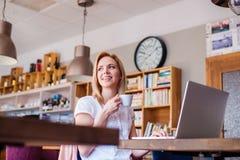 Blonde Frau mit Notizbuch in trinkendem Kaffee des Cafés Stockfotos