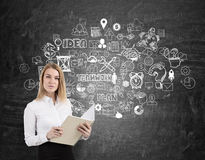 Blonde Frau mit Notizbuch- und Teamwork-Skizze auf einer Tafel Lizenzfreie Stockbilder