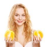 Blonde Frau mit Orangen in ihren Händen Lizenzfreie Stockfotos
