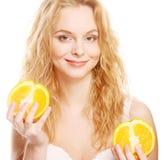 Blonde Frau mit Orangen in ihren Händen Lizenzfreie Stockbilder