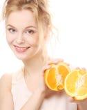 Blonde Frau mit Orangen in ihren Händen Stockbilder