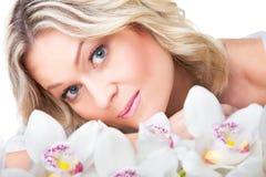 Blonde Frau mit Orchidee auf getrenntem Weiß Lizenzfreies Stockfoto