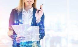 Blonde Frau mit Papieren in einem Büro Lizenzfreie Stockbilder