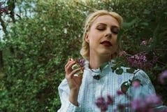 Blonde Frau mit Parfüm im Garten nahe der Flieder Lizenzfreies Stockbild